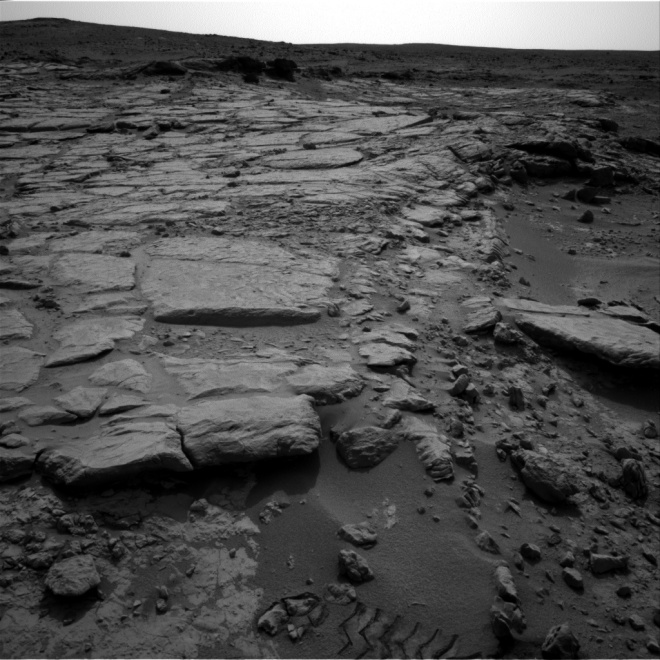 In this black and white image from the mast camera on Curiosity you can see how the ground is no flat here but has considerable relief.  Image Credit: NASA/JPL-Caltech