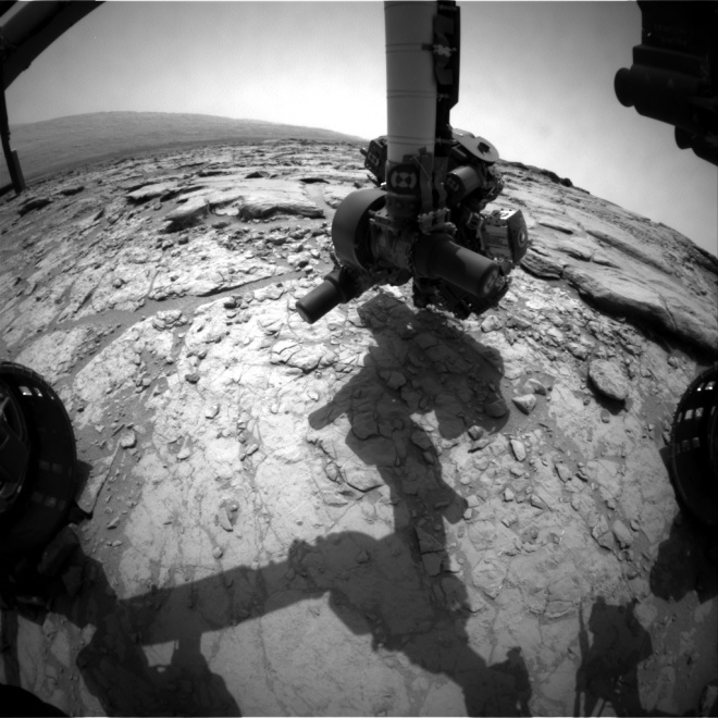 An image from the front hazard camera on Curiosity from today's location showing the instrument arm extending down to inspect the rocks in front of the rover.  Image Credit: NASA/JPL-CalTech