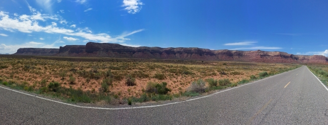 A panorama image taken with my phone of route 261 heading north of the Goosenecks of the San Juan River.  In the distance is the plateau which we would need to climb to get to Muley Point which is on the left end.  Photo credit: Joel Duff