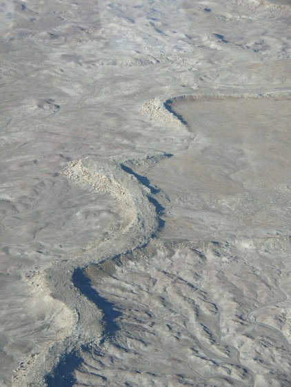 An oblique aerial photograph of a carbonate-cemented, sinuous inverted paleochannel segment located approximately 11 kilometers southwest of Green River, Utah.