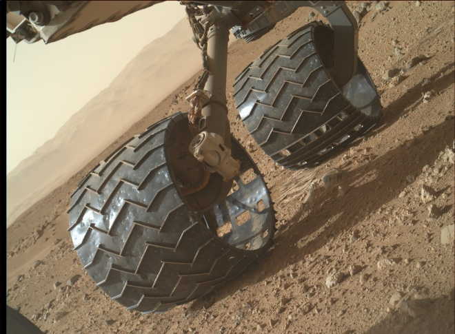 A view from under the Curiosity rover showing two of its six wheels. If you look closely you can see that they have many small pits in the aluminum showing the wear and tear they have received from driving on this rocky ground. Image: JPL/NASA-CalTech
