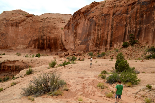 Hiking back from Corona Arch near Moab UT.  Notice the desert varnish on the walls but not on the horizontal rocks.  A couple of my kids are in the foreground for scale.  Image: Joel Duff