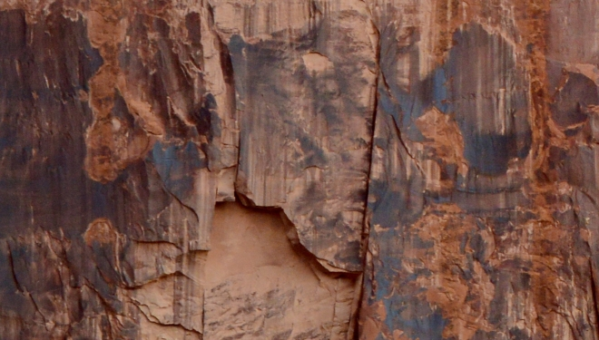 Close-up of sandstone wall along the Colorado River showing where a piece of the rock has fallen off revealing sandstone without desert varnish.  The relative ages of the rock surfaces can be gauged by the amount of varnish on the surface.  Image credit: Joel Duff
