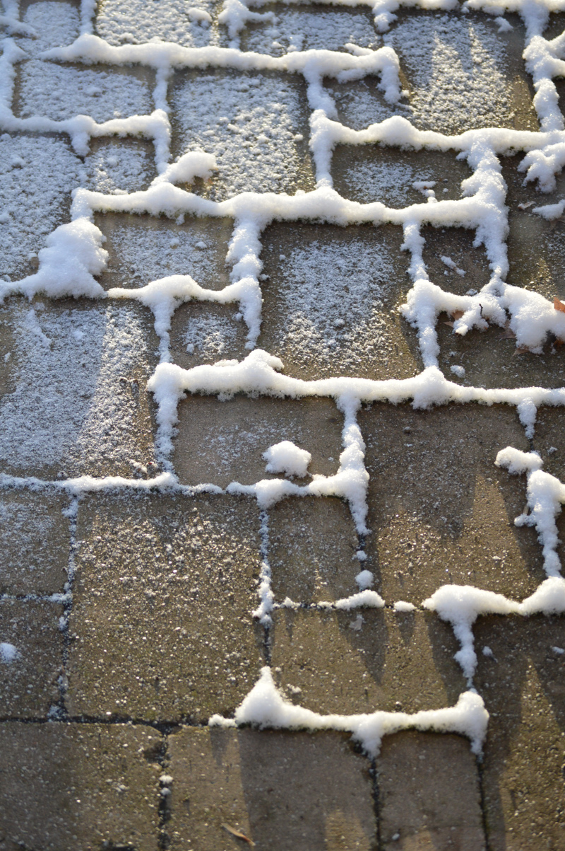 The First Rays Of Sunlight Strike Snow On Our Patio Stones. The House Is  Closest