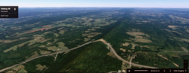The road cut through Sideling Hill as viewed by a screenshot of a Google Earth video.  Sidling Hill runs to the north into Pennsylvania in this picture.  Image: Google Inc.
