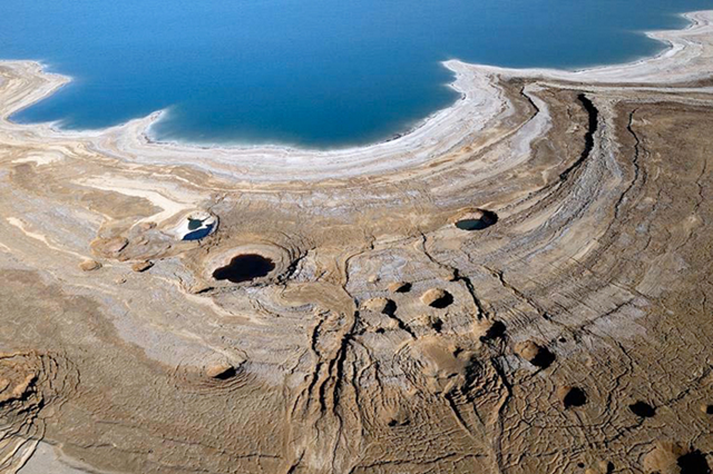 Sinkholes along the shores of the Dead Sea.  these form when layers of salt beneath the ground dissolve in groundwater creating underground caverns.