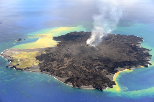 The new volcano (black material) is taking over the old island (green and yellow portion of the island).