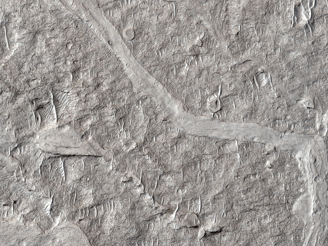 HiRise satelite image of the surface of Mars showing small sand dunes covering an ancient landscape that probably once has a valley of some sort. Maybe a river. Image: NASA/JPL/University of Arizona