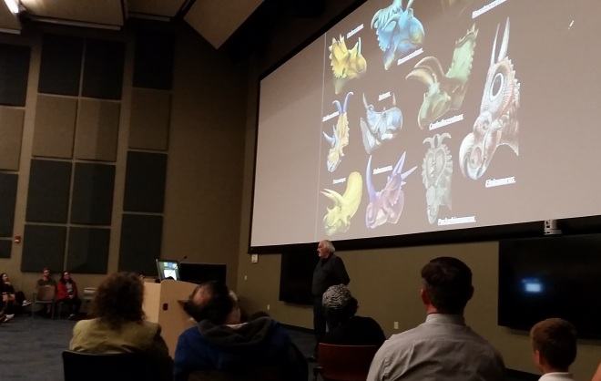 Dr. Horner speaking about dinosaur accoutrements. A packed house for Dr. Horner's talk. Extra chairs were set up on the side next to the screen. We were in the front row of regular seats but way over to the side.